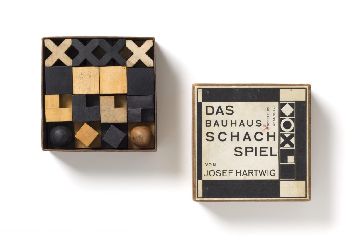 Josef Hartwig (1880–1955), Joost Schmidt (1893–1948) Schachspiel, Modell XVI/Chess set, model XVI, 1923/24, Birnenholz, naturfarben und schwarz gebeizt; Karton, mit Papier überzogen, bedrucktes Papieretikett/Pear wood, natural and stained black; cardboard covered with paper, printed paper label Figuren/Pieces: 2×2×2 cm – 4,8×2,8×2,8 cm, Schachtel/Box: 5×12,5×12,5 cm Spielbrett/Chessboard: 43×42,5 cm, Hersteller/Producer: Bauhaus Weimar, Provenienz/Provenance: Michael Hennig, Berlin Ankauf mit Unterstützung der/Acquisition with the support of the Ernst von Siemens Kunststiftung, 2018, Inv.-Nr. 301/2018, Foto: Die Neue Sammlung (A.Laurenzo) © VG-Bild, Bonn 2019
