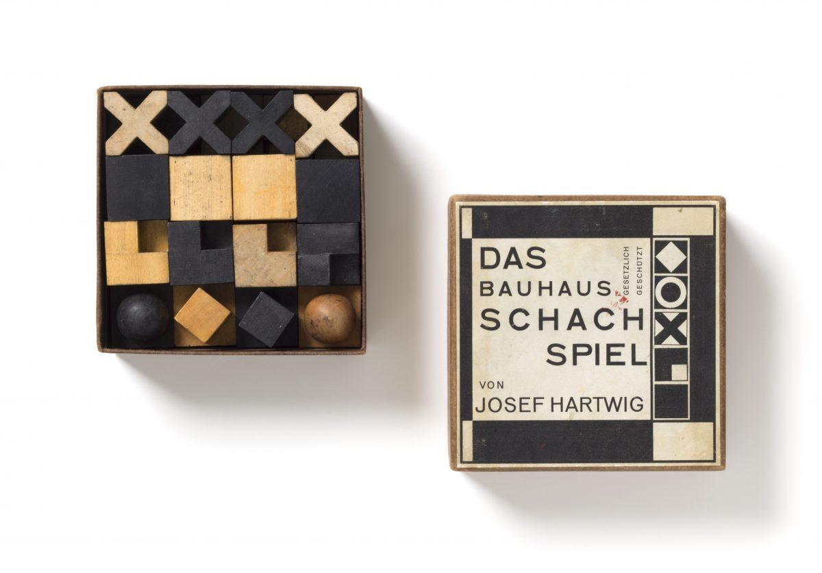 Josef Hartwig (1880–1955), Joost Schmidt (1893–1948) Schachspiel, Modell XVI/Chess set, model XVI, 1923/24, Birnenholz, naturfarben und schwarz gebeizt; Karton, mit Papier überzogen, bedrucktes Papieretikett/Pear wood, natural and stained black; cardboard covered with paper, printed paper label Figuren/Pieces: 2×2×2 cm – 4,8×2,8×2,8 cm, Schachtel/Box: 5×12,5×12,5 cm Spielbrett/Chessboard: 43×42,5 cm, Hersteller/Producer: Bauhaus Weimar, Provenienz/Provenance: Michael Hennig, Berlin Ankauf mit Unterstützung der/Acquisition with the support of the Ernst von Siemens Kunststiftung, 2018, Inv.-Nr. 301/2018, Foto: Die Neue Sammlung (A.Laurenzo) © VG-Bild, Bonn 2019